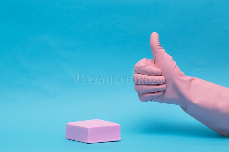 Żeńska ręka w różowej gumowej rękawiczce z nastroszonym w górę palca na błękitnym tle, zdjęcie royalty free