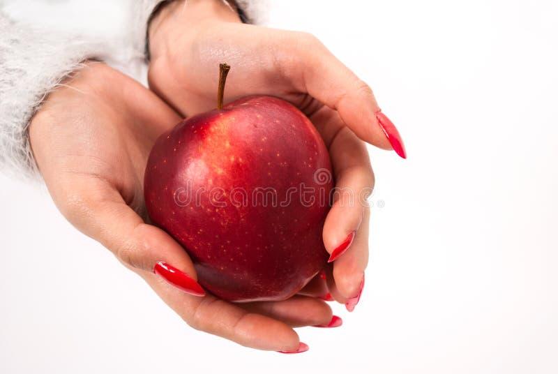 Żeńska ręka w zakończeniu w górę mienia czerwonego jabłka odizolowywającego na białym tle zdjęcie royalty free