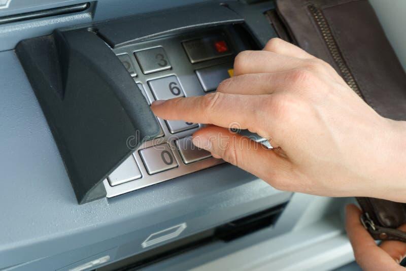 Żeńska ręka wchodzić do bezpiecznie WAŁKOWEGO kod przy i w szczególe up gotówkowym punktem lub ATM zakończeniem obraz stock