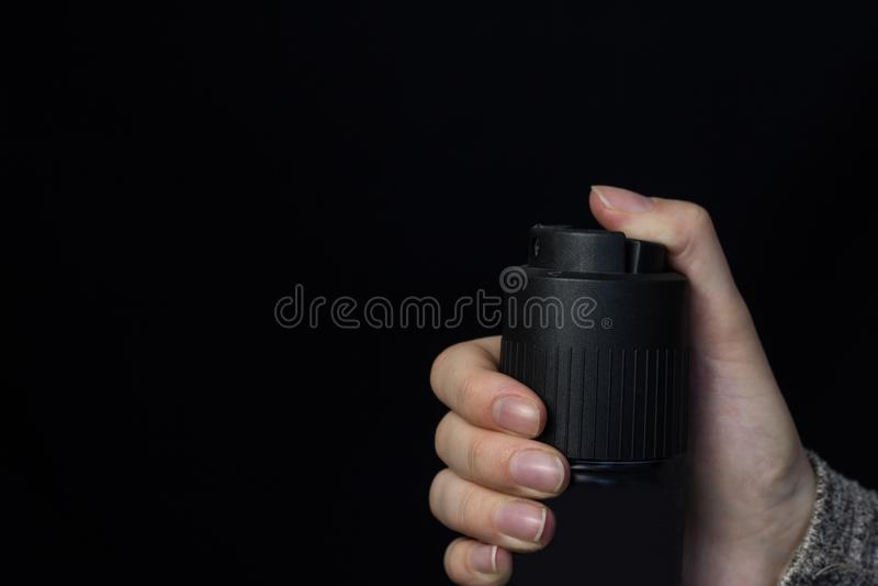 Żeńska ręka z benzynową kiścią na czarnym tle, zakończenie obrazy stock