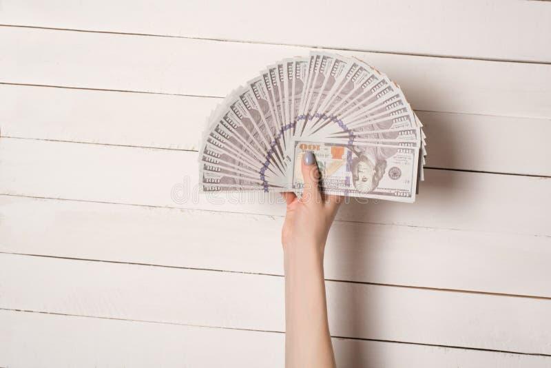 Żeńska ręka z fan 100 dolarowych Amerykańskich banknotów na białym drewnianym stołowym tle zdjęcie royalty free