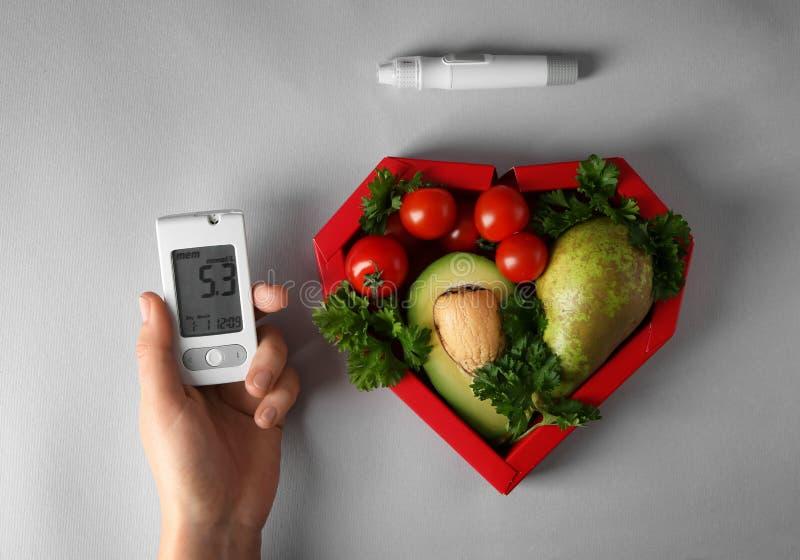 Żeńska ręka z glucometer, lancetu piórem i zdrowym jedzeniem na popielatym tle, Cukrzycy dieta fotografia royalty free