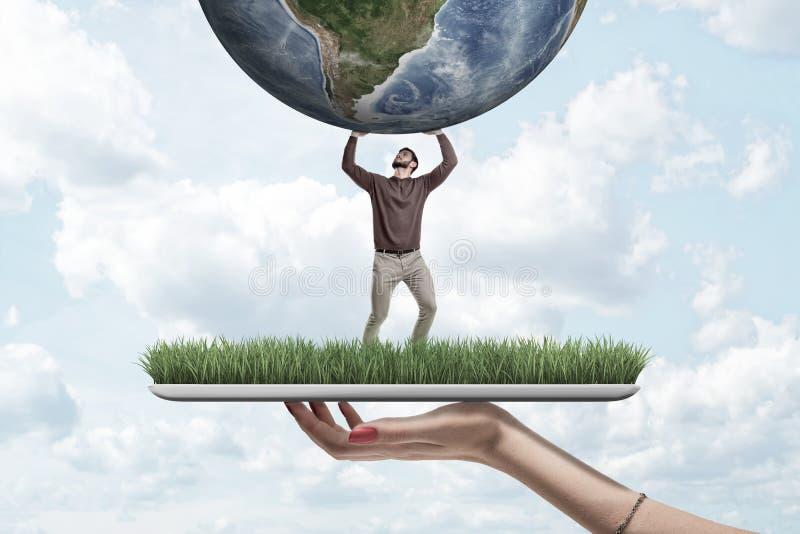 Żeńska ręka z małym mężczyzną trzyma ziemską kulę ziemską na zielonej trawy modelu z niebieskiego nieba tłem w przypadkowych ubra zdjęcia royalty free