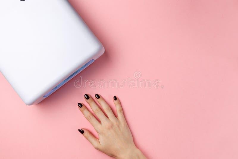 Żeńska ręka z robiącymi manikiur gwoździami i ULTRAFIOLETOWĄ lampą obraz stock
