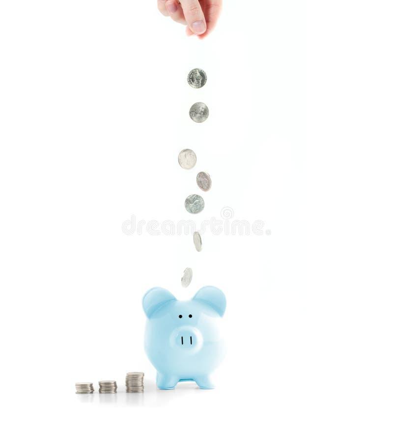 Żeńska ręki kładzenia moneta w prosiątko banka na bielu obrazy stock