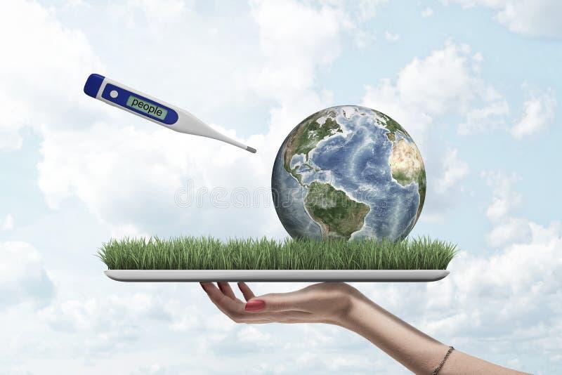 Żeńska ręki mienia ziemi kula ziemska i cyfrowy termometr z ludźmi podpisujemy na zielonej trawy modelu na niebieskiego nieba tle royalty ilustracja