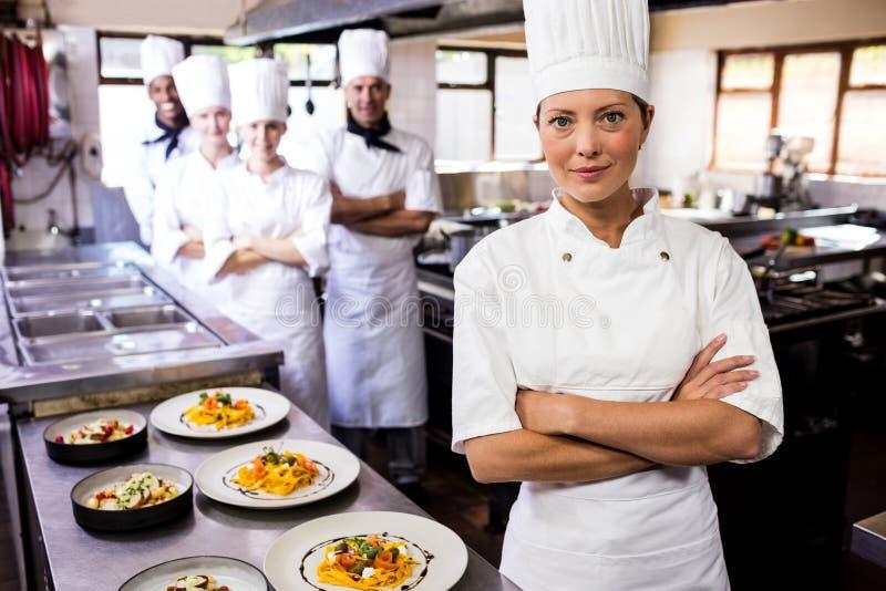 Żeńska szef kuchni pozycja z rękami krzyżował w kuchni obrazy stock