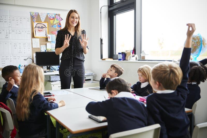 Żeńska szkoła podstawowa nauczyciela pozycja w sali lekcyjnej gestykuluje ucznie siedzi przy stołowym słuchaniem, jeden podnosić  fotografia royalty free