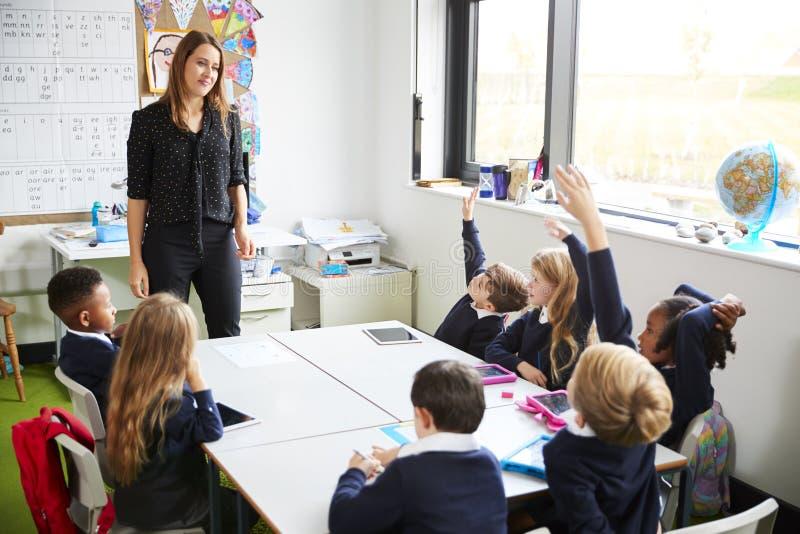 Żeńska szkoła podstawowa nauczyciela pozycja w sali lekcyjnej i ucznie siedzi przy stołem podnosi ich ręki obraz royalty free
