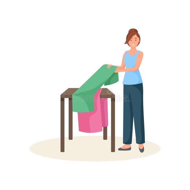 Żeńska szwaczka stoi blisko stołu i składa płótno odizolowywającego na białym tle ilustracji