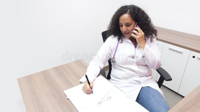 Żeński łaciński kobiety lekarki obsiadanie relaksuje w jej ordynacyjnym pokoju z stetoskopem na jej szyi opowiada jej mądrze tele fotografia royalty free