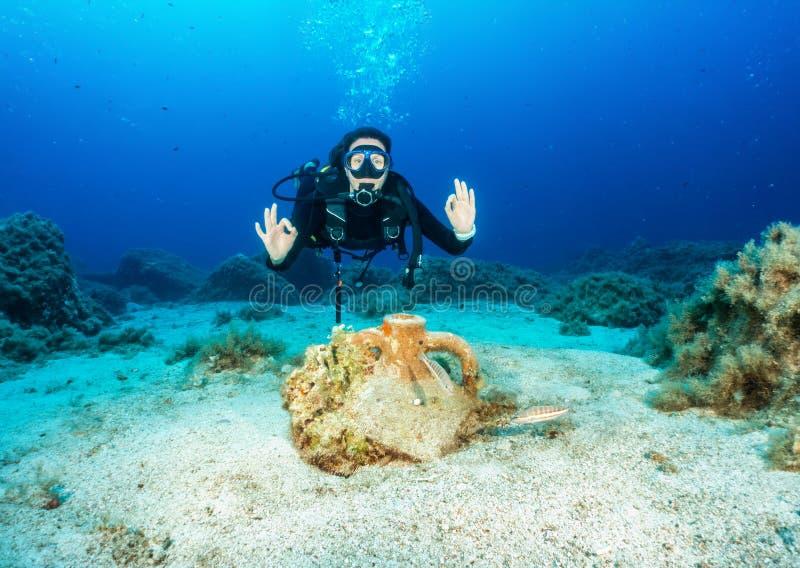 Żeński akwalungu nurek przed starożytnym grkiem, zapadnięta amfora w morzu egejskim fotografia royalty free