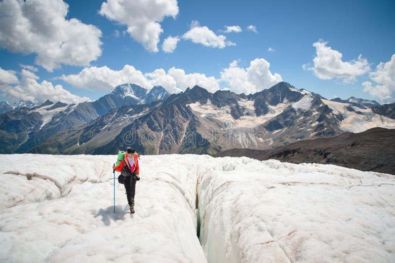 Żeński alpinista cieszy się piękno lodowiec chodzi na lodowu w okularach przeciwsłonecznych i crampon Przeciw zdjęcia royalty free