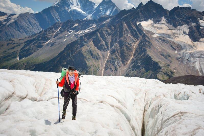 Żeński alpinista cieszy się piękno lodowiec chodzi na lodowu w okularach przeciwsłonecznych i crampon Przeciw zdjęcia stock