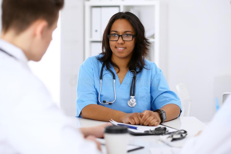 Żeński amerykanina afrykańskiego pochodzenia lekarz medycyny z kolegami w tle przy szpitalem Medycyny i opieki zdrowotnej pojęcie zdjęcia royalty free