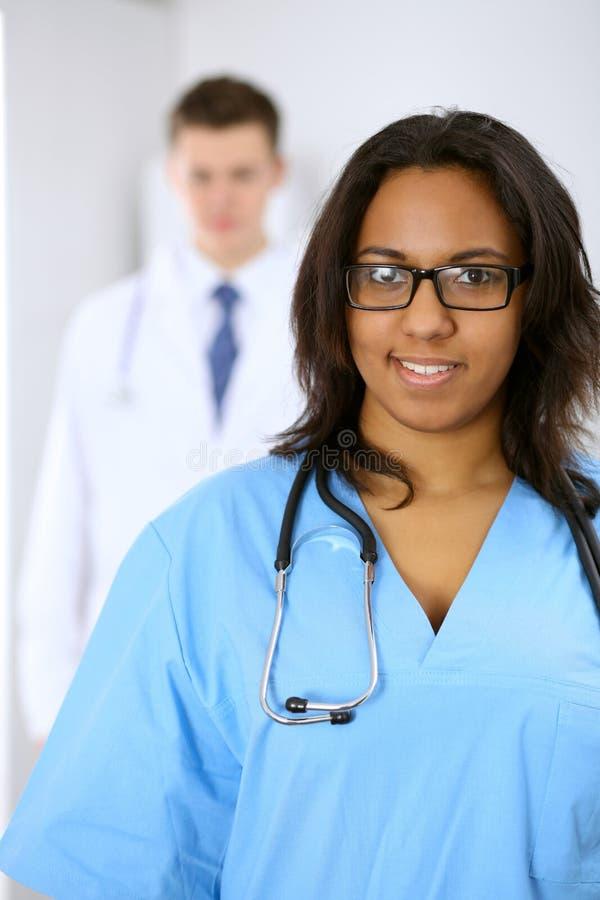Żeński amerykanina afrykańskiego pochodzenia lekarz medycyny z kolegami w tle przy szpitalem Medycyny i opieki zdrowotnej pojęcie obrazy stock