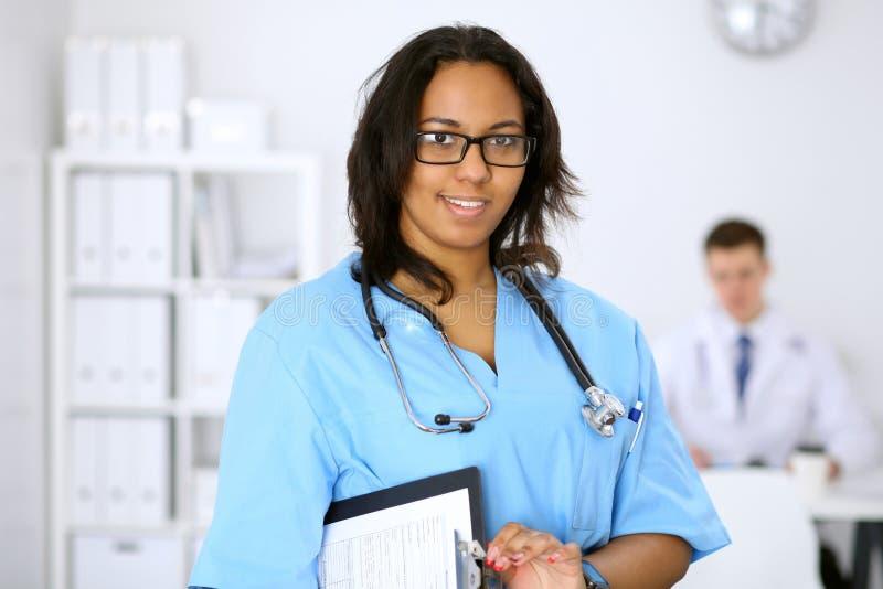 Żeński amerykanina afrykańskiego pochodzenia lekarz medycyny z kolegami w tle przy szpitalem Medycyny i opieki zdrowotnej pojęcie obrazy royalty free