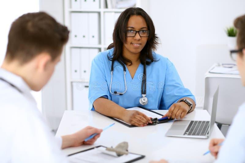 Żeński amerykanina afrykańskiego pochodzenia lekarz medycyny z kolegami w tle przy szpitalem Medycyny i opieki zdrowotnej pojęcie obraz stock