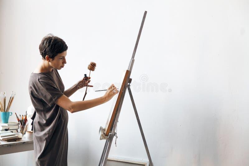 Żeński artysta w jej przestronnym białym pracownianym działaniu z akwarela obrazem obraz stock