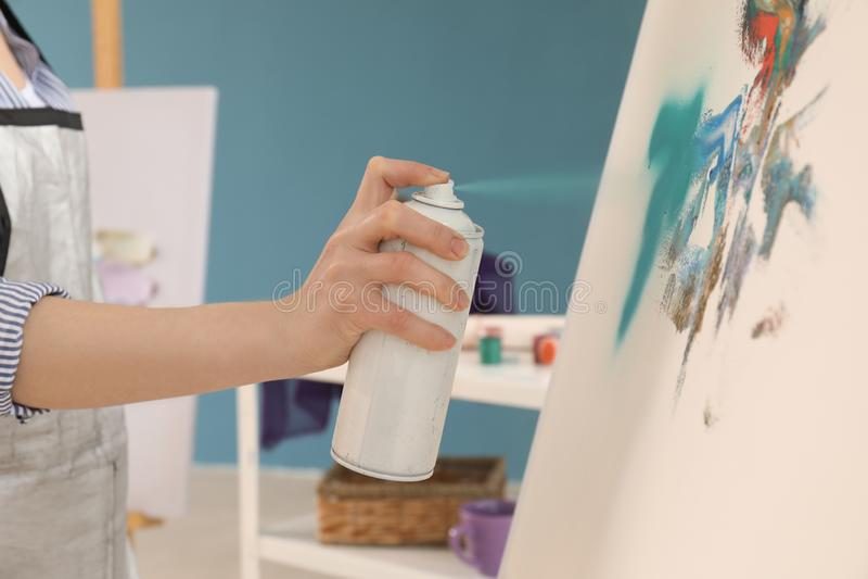 Żeński artysty obraz z aerosolową kiścią w warsztacie zdjęcia stock