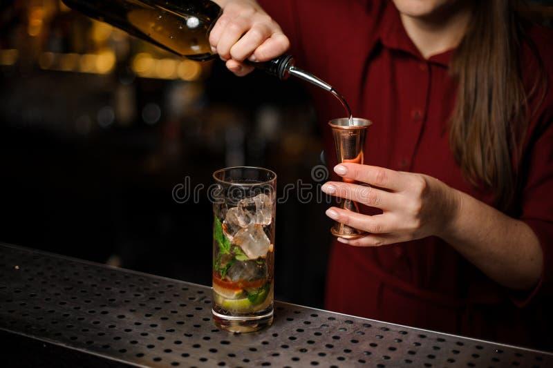 Żeński barman wypełnia liqour pomiarowy stos fotografia royalty free