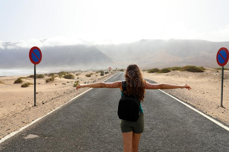Żeński beztroski backpacker cieszy się krajobraz po środku pustynnej asfaltowej drogi zdjęcie stock