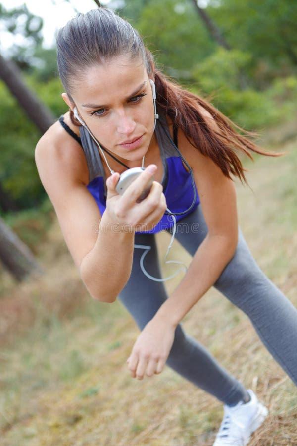 Żeński biegacz patrzeje sporta zegarek fotografia stock