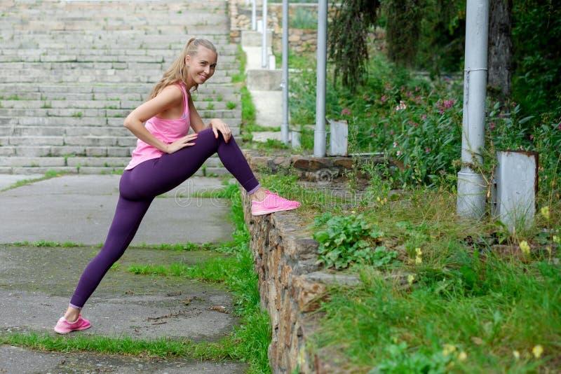 Żeński biegacz z piękną postacią robi rozciągania ćwiczeniu zdjęcia stock