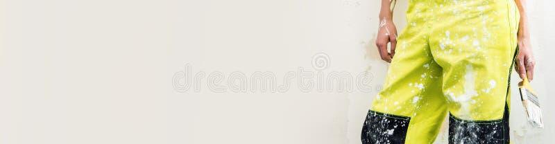 Żeński budowniczy w coverall chwyta farby muśnięciu nad panoramicznym tłem obraz stock