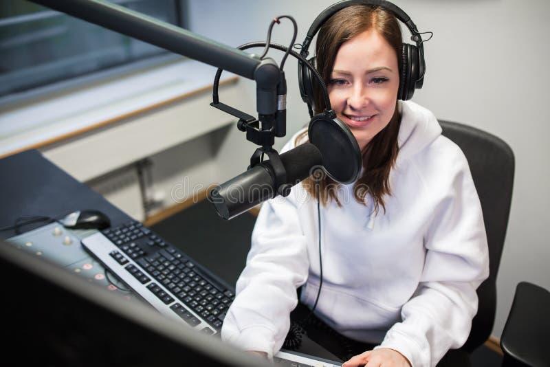 Żeński dżokej ono uśmiecha się podczas gdy komunikujący na mikrofonie w radiu zdjęcie stock