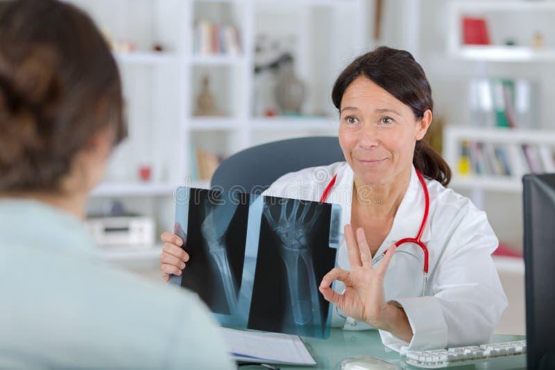 Żeński dentysta pokazuje promieniowania rentgenowskie pacjent zdjęcia stock
