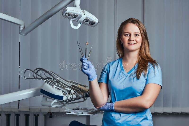 Żeński dentysta trzyma stomatologicznych narzędzia podczas gdy siedzący w jej dentysty biurze obrazy stock
