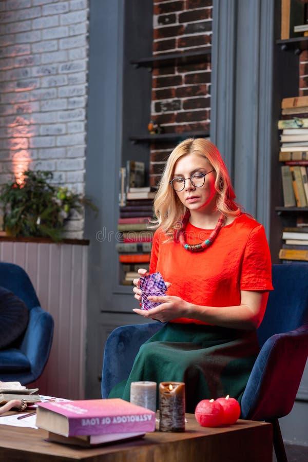 Żeński diviner jest ubranym szkła czuje inspirowane czytelnicze wróżb karty zdjęcie stock