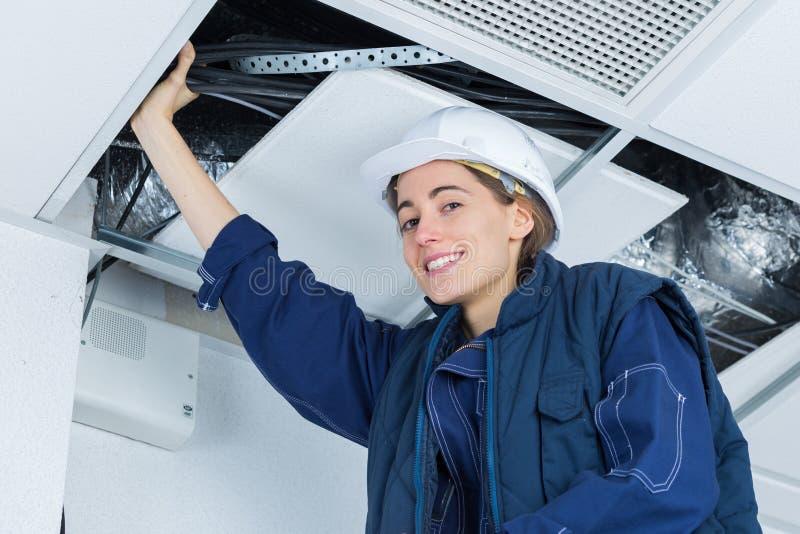 Żeński elektryk instaluje elektrycznego przyrząd w suficie obraz stock