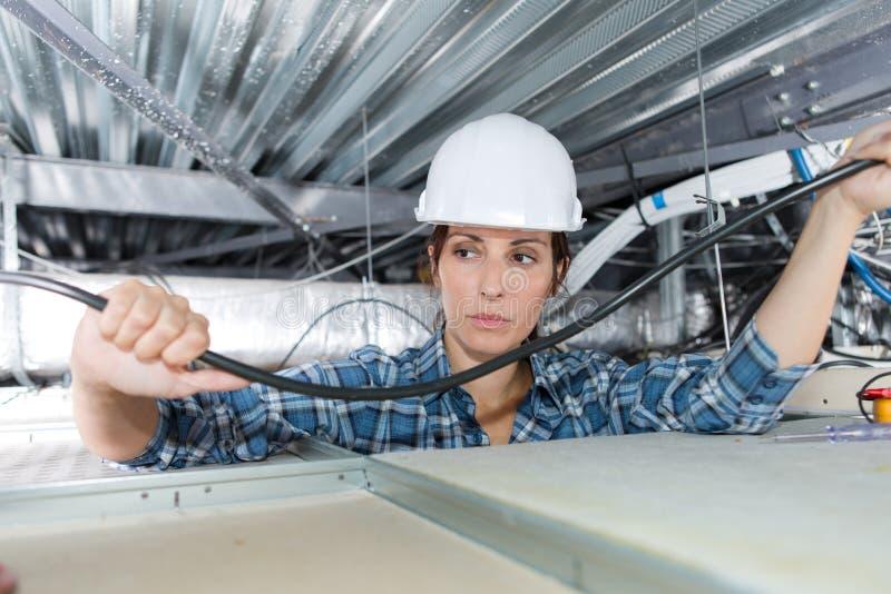 Żeński elektryka drutowanie w budynku suficie obraz royalty free