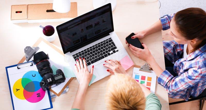 Żeński fotografa obsiadanie na biurku z laptopem obraz stock