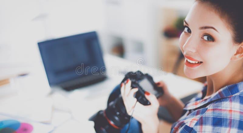 Żeński fotografa obsiadanie na biurku z laptopem obrazy stock