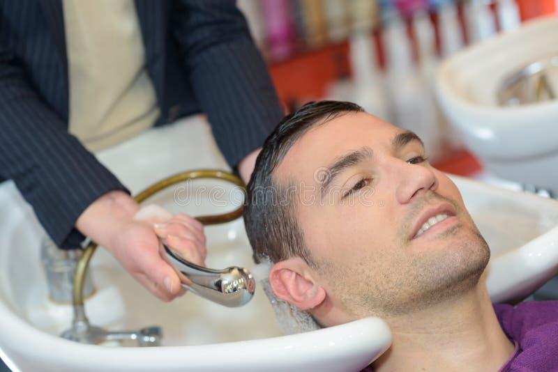 Żeński fryzjer myje przystojnych klientów włosianych obrazy royalty free