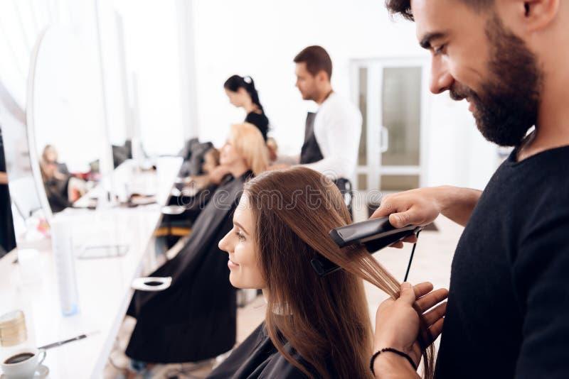 Żeński fryzjer prostuje brown włosy ładna kobieta używa włosy żelazo w piękno salonie obraz stock