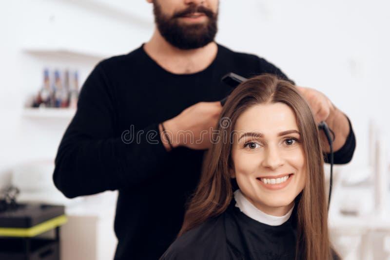 Żeński fryzjer prostuje brown włosy ładna kobieta używa włosy żelazo w piękno salonie obrazy royalty free