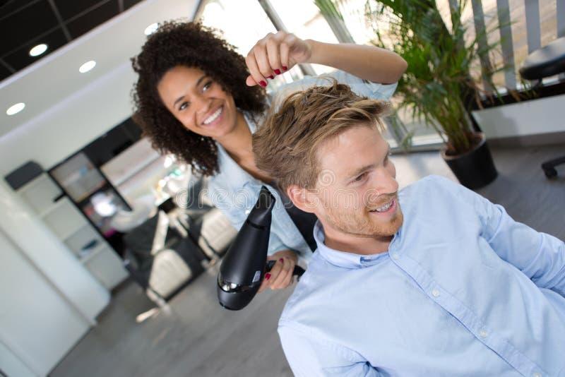 Żeński hairstylist ma zabawę z klientem zdjęcie royalty free