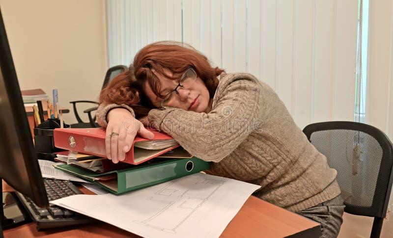 Żeński kierownik spadać uśpionego w miejscu pracy przy biurem obraz stock