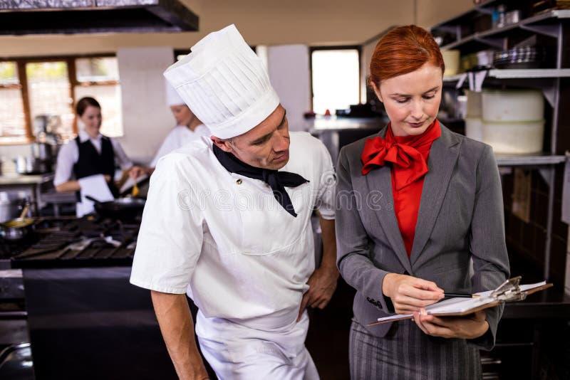 Żeński kierownika i samiec szef kuchni pisze na schowku w kuchni fotografia royalty free