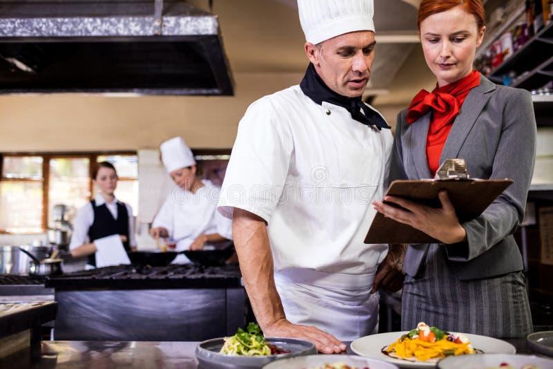 Żeński kierownika i samiec szef kuchni pisze na schowku w kuchni zdjęcie stock