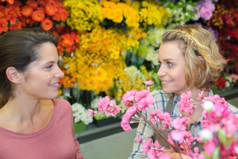 Żeński klient z kwiaciarnią przy kwiatu sklepem obrazy stock