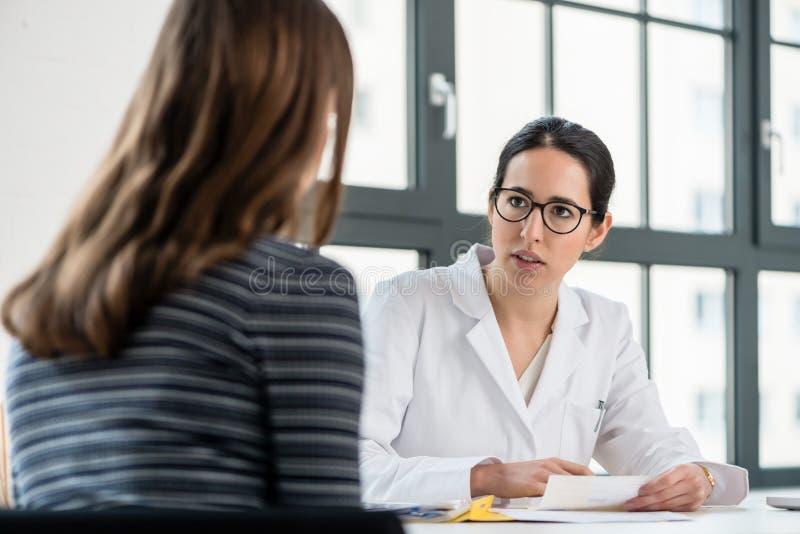 Żeński lekarz słucha jej pacjent podczas konsultaci zdjęcia royalty free