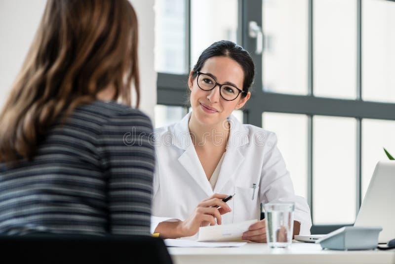 Żeński lekarz słucha jej pacjent podczas konsultaci obraz stock