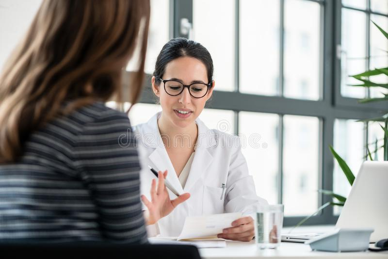 Żeński lekarz słucha jej pacjent podczas konsultaci wewnątrz zdjęcie stock