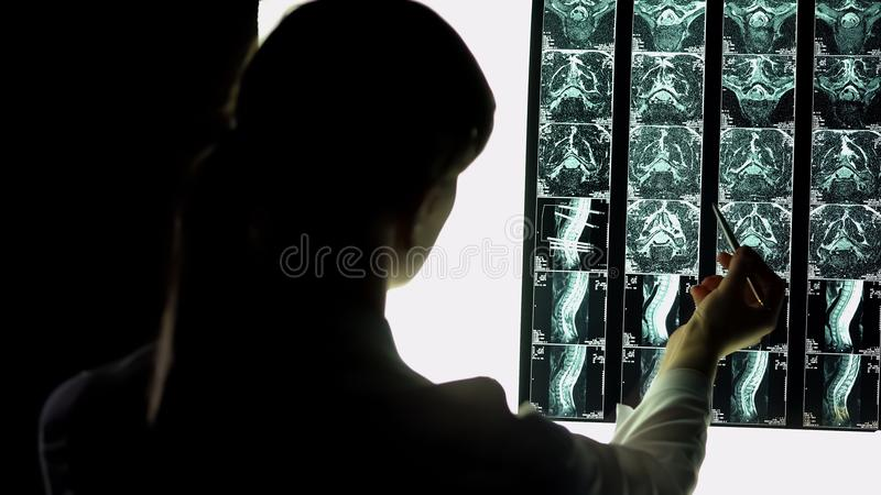 Żeński lekarz szpitalny attentively sprawdza cierpliwego promieniowanie rentgenowskie, urazu egzamin zdjęcie stock