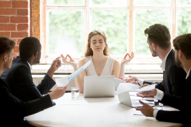 Żeński lider medytuje ignorujący gniewnych coworkers obrazy stock